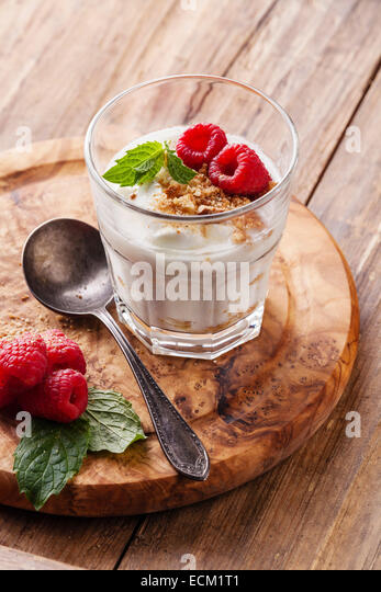 Glass of delicious yogurt muesli with raspberries on wooden background - Stock Image