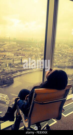 Depressed Business Woman Sitting On Chair In Front Of Office Window At City - Stock Image