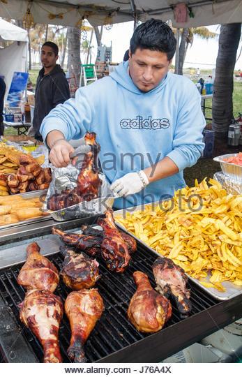 Miami Beach Florida Ocean Drive Art Deco Weekend festival fair food vendor Hispanic man cook turkey legs - Stock Image