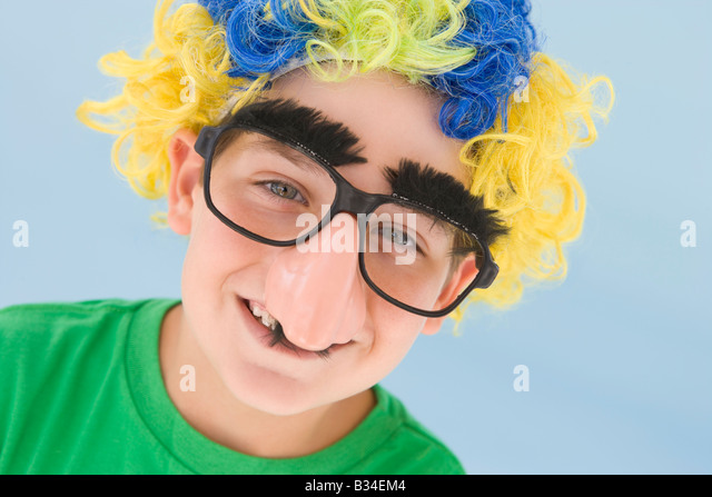 Young boy wearing clown wig and fake nose smiling - Stock Image