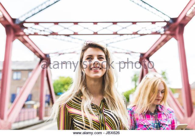 Two female friends walking on bridge, girl in background using smartphone - Stock-Bilder