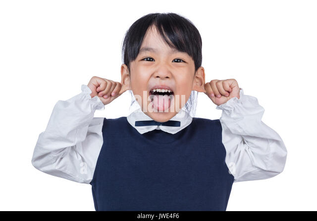 Asian Little Chinese Girl pulling ears and making a grimace in isolated White Background - Stock Image