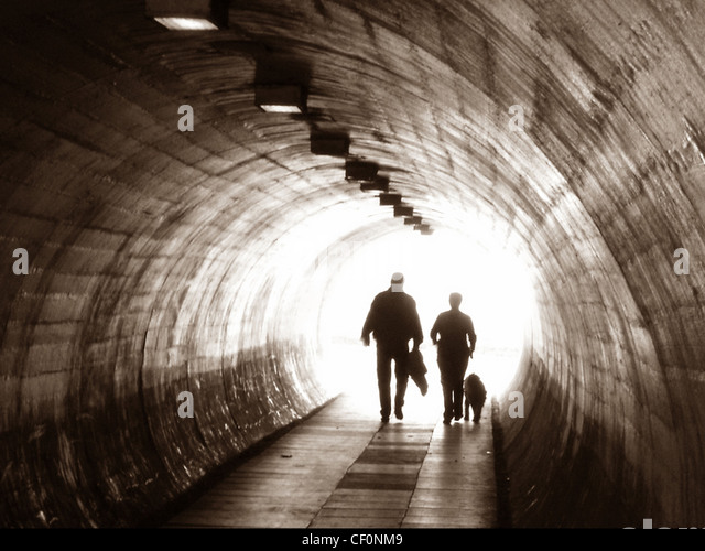 Two people and a dog walking through a tunnel at  Latchford (off Kingsway), Warrington , Cheshire , England, UK - Stock Image
