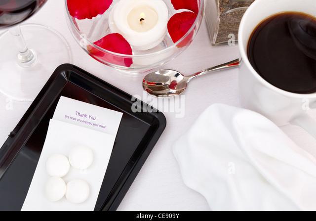 Still life photo of a restaurant bill / check / till receipt on a tray - Stock Image