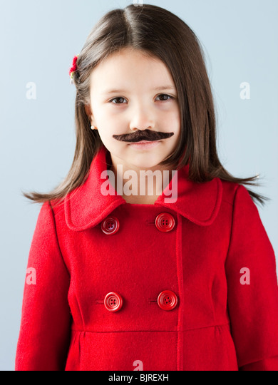 Girl (6-7) in red coat wearing fake mustache, portrait - Stock Image