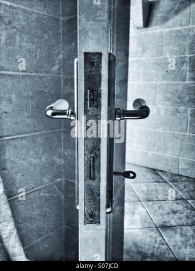 Interior open door with both sides showing handles and key in lock - Stock Image