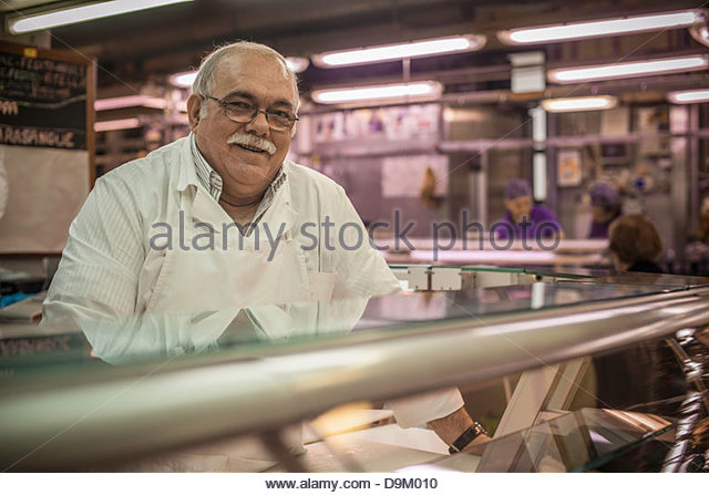 Man at counter in market - Stock Image