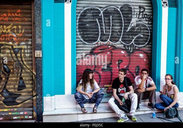 Spain Europe Spanish Madrid Centro Lavapias Calle Argumosa young adults man woman couple sitting graffiti - Stock Image