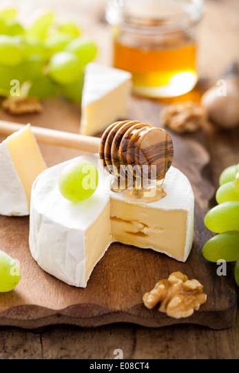 camembert cheese with grapes, honey and nuts on wooden background - Stock Image