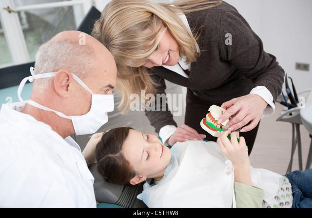 Germany, Bavaria, Landsberg, Mother showing girl (8-9) how to brush teeth, dentist beside - Stock-Bilder