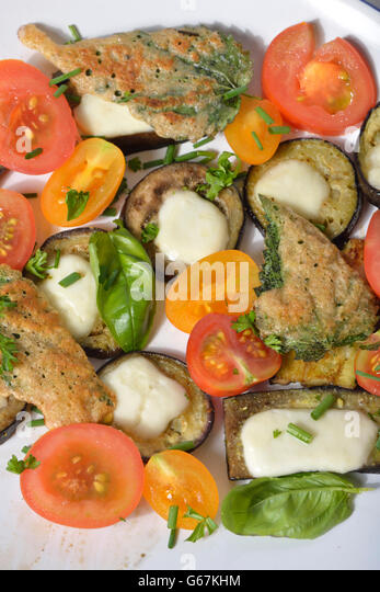 Plate with tomatoes, aubergine, baked nettle leaves - Stock Image