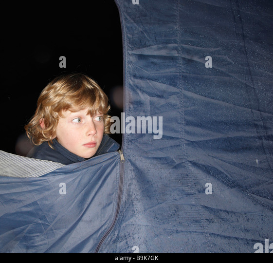 Boy looking out of tent at dusk - Stock Image