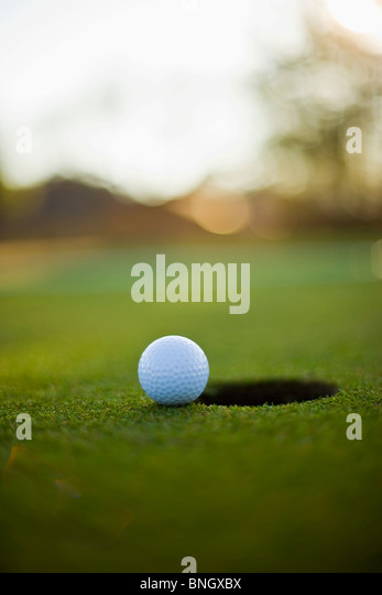 Close-up of a golf ball near a hole - Stock Image