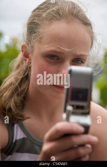 Young girl (12) texting on a mobile phone, close-up - Stock Image