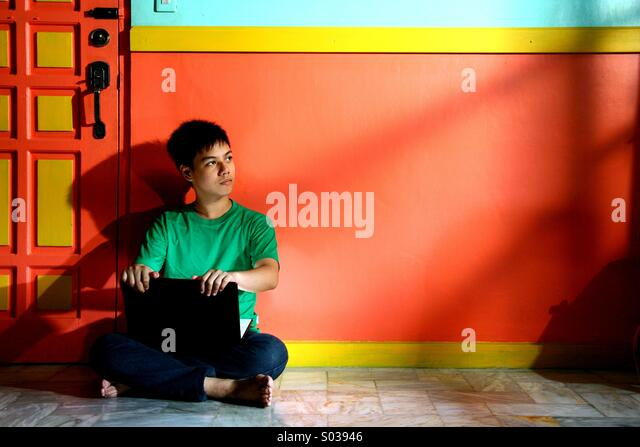 Young asian teen with a laptop computer in an empty living room - Stock Image
