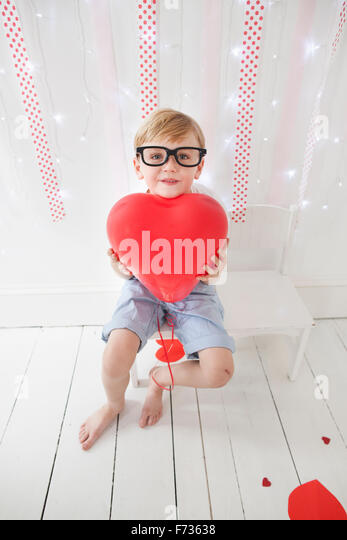 Young boy posing for a picture in a photographers studio, holding red balloons. - Stock Image