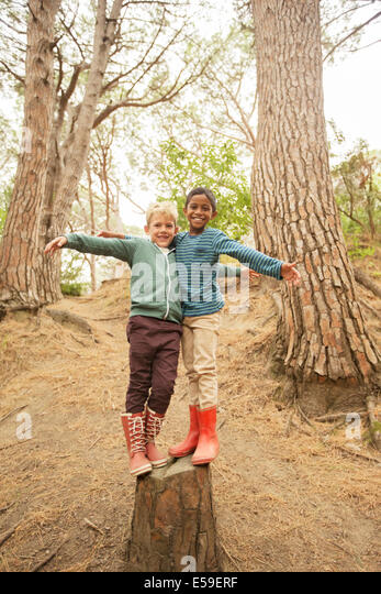 Children climbing on stump in forest - Stock Image