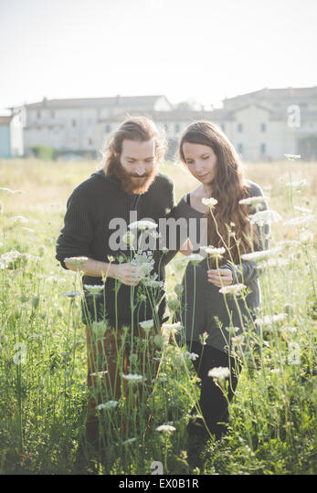Young couple picking wild flowers in field - Stock-Bilder