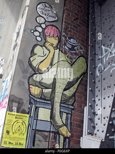 Berlin Mitte,Street art on walls,Germany- Girl sits crosslegged on table What Color Has The Love? - Stock Image