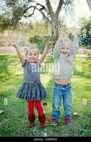 Brother and sister with arms raised, in garden - Stock Image