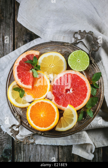Vintage silver plate with set of sliced citrus fruits lemon, lime, orange, grapefruit over wooden table. Top view. - Stock Image