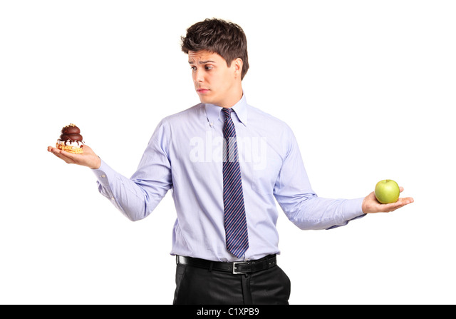 A man holding an apple and slice of cake trying to decide which one to eat - Stock Image