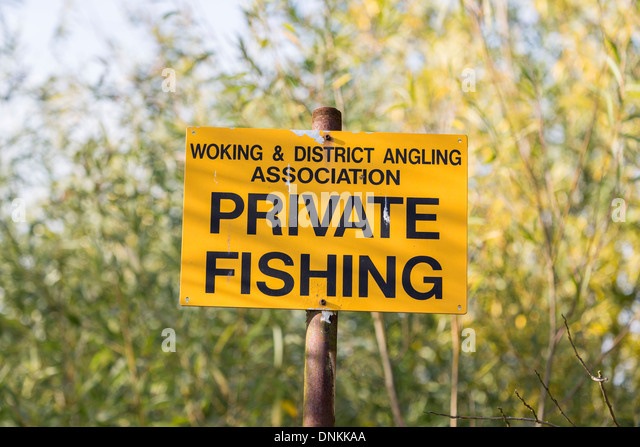 Yellow and black sign on River Wey in Pyrford, Surrey, UK: Woking & District Angling Association Private Fishing - Stock Image