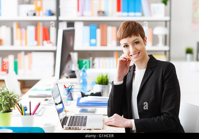 Confident successful businesswoman sitting at office desk and working with a laptop, she is smiling at camera - Stock Image