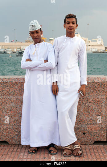 Young Omani men in traditional outfits on the Mutrah promenade in Muscat, the capital of the Sultanate of Oman. - Stock-Bilder