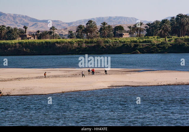 Boys and men playing soccer on a spit of land in the Nile River, Egypt - Stock-Bilder