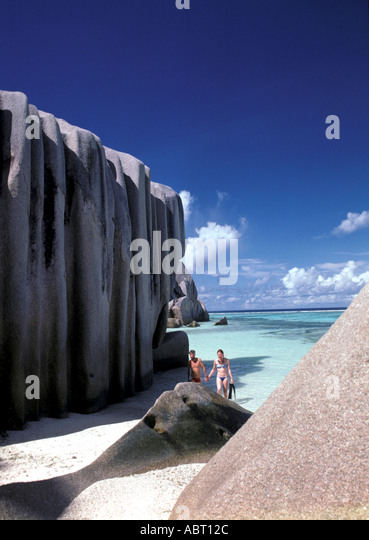 Seychelles Island of La Digue Snorkeling couple surrounded by large boulders - Stock Image