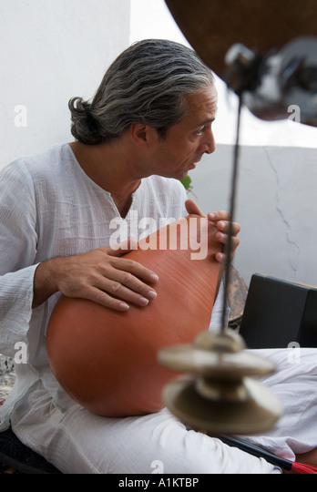 musician plays large clay percussion instrument - Stock-Bilder