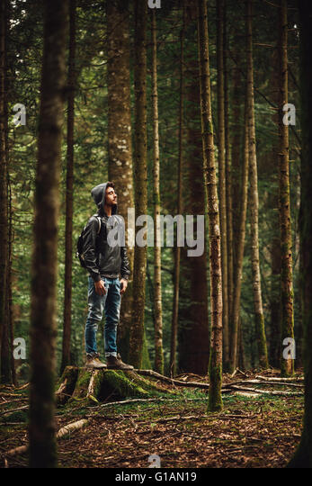 Hooded young man standing in the forest and exploring, freedom and nature concept - Stock-Bilder