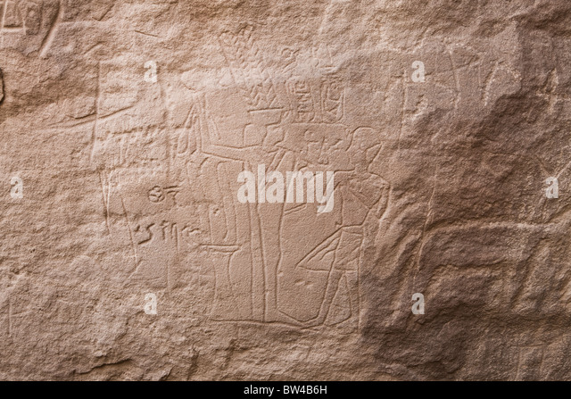 Depiction of Amenhotep before Min  etched in rock-face  in Wadi Mineh in Eastern Desert of Egypt - Stock Image