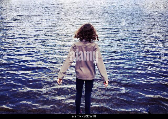 Young girl looking out over lake with her arms outstretched - Stock Image