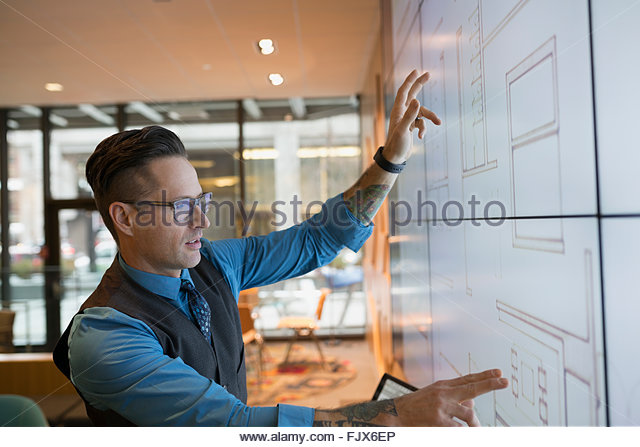 Architect using projection screen in conference room - Stock Image