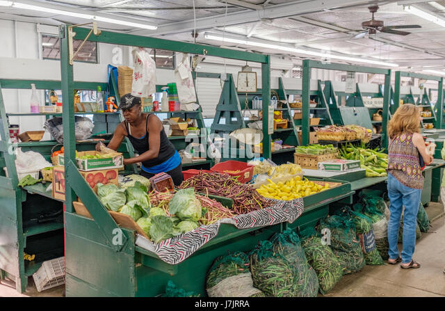 Shoppers at a local farmers market buying fruits and vegetables. - Stock Image