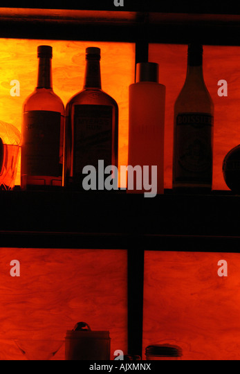 Silhouette of Back Lit Bottles of Liquor on Shelves with Copy Space - Stock Image