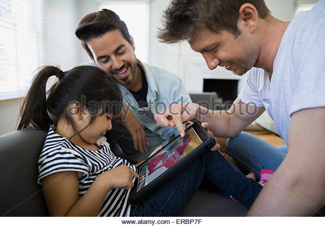 Homosexual couple and daughter using digital tablet - Stock Image