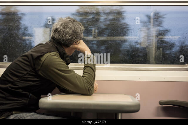 Middle aged man looking out of train window. Rain on window. UK - Stock Image