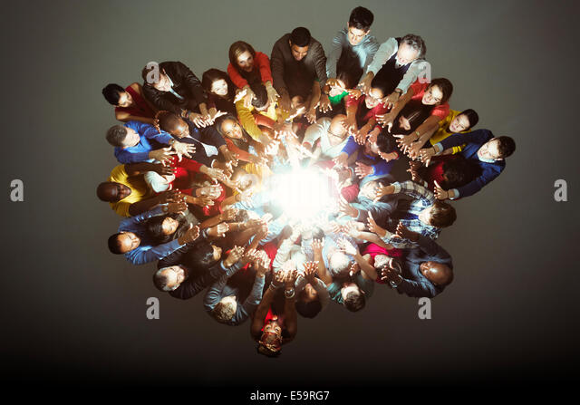 Diverse workers around bright light - Stock Image