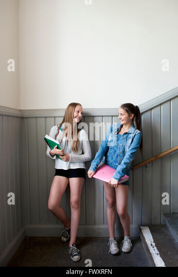 Two girls (14-15) standing against wall - Stock Image