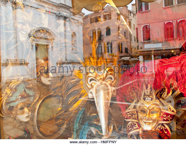 Ornate Venetian masks for Venice Carnival on display in shop window with architectural reflection, Italy - Stock-Bilder
