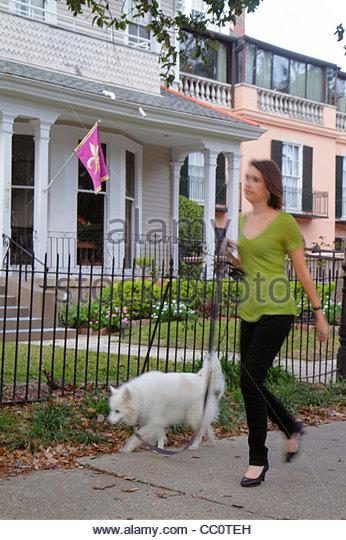 Louisiana New Orleans Garden District Washington Avenue National Historic District neighborhood house fence woman - Stock Image