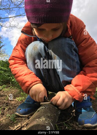 Boy making wooden beads with pocket knife - Stock-Bilder