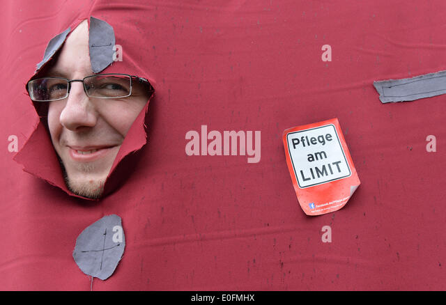 Bremen, Germany. 12th May, 2014. A demonstrator looks through a hole in a piece of cloth next to a sticker which - Stock Image