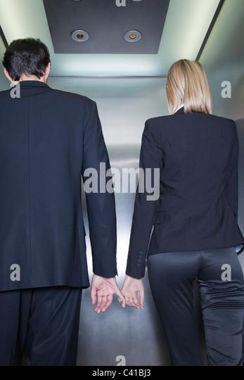Professionals holding hands in elevator, rear view - Stock-Bilder