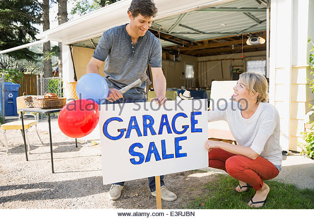 Couple putting up garage sale sign in yard - Stock Image