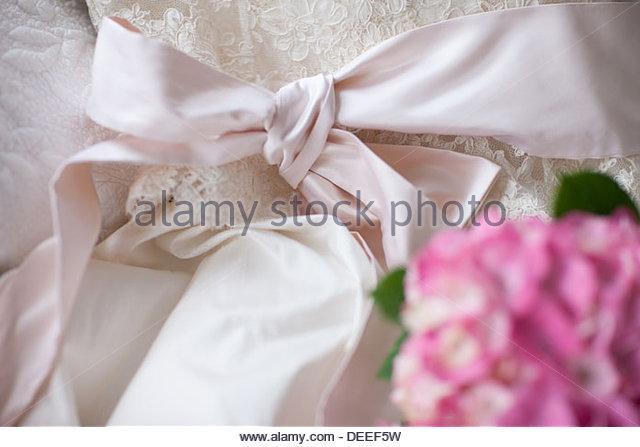 Pink hydrangea on wedding dress - Stock Image