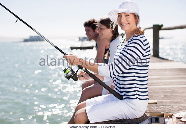 Friends fishing off pier at ocean - Stock Image